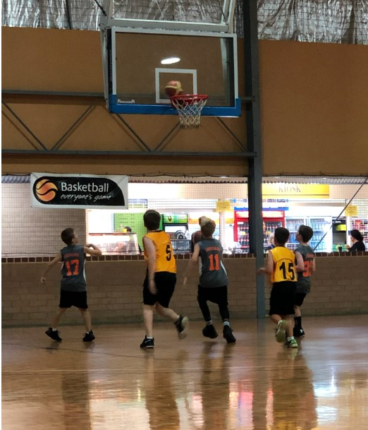young boys team playing basketball match
